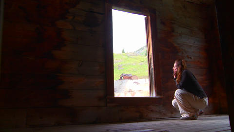 A woman sits in an abandoned house looking out the Stock Video Footage
