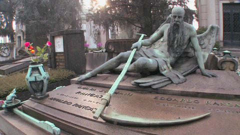 The grim reaper sits on a tomb in a graveyard with Stock Video Footage