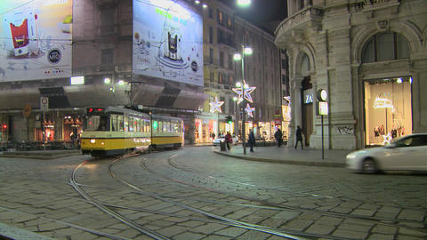A trolley passes at night on a street in Milan, It Stock Video Footage
