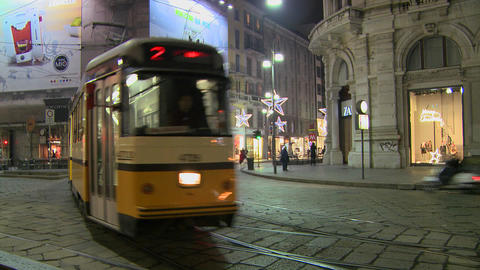 A trolley passes at night on a street in Milan, It Footage