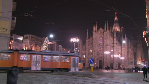A trolley passes at night on a street in front of Stock Video Footage