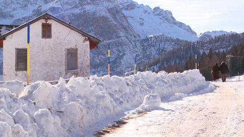 An old couple walks down a snow covered road in th Stock Video Footage