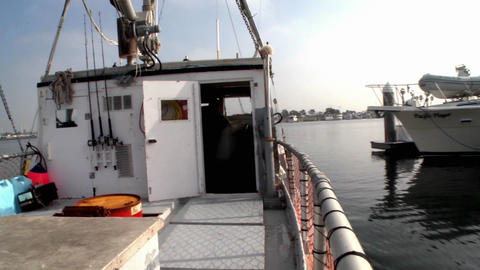 A boat passes through a marina where many boats are docked Stock Video Footage