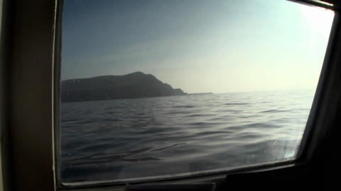 An island is viewed through the porthole of a boat Stock Video Footage