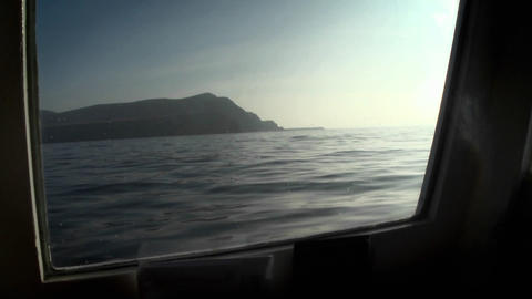 An island is viewed through the porthole of a boat Footage