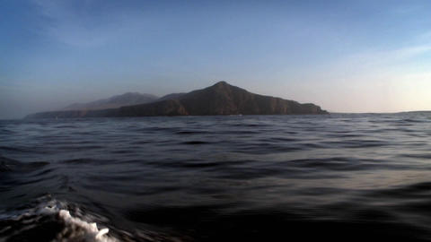 A boat sails through the water, with mountains in the distance Footage