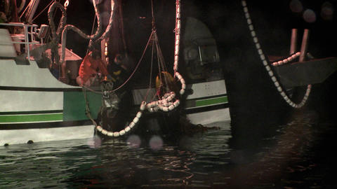 A crew member reaches into a fishing vessels net Live Action