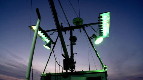 A fishing vessel turns on its outside flood lights Stock Video Footage