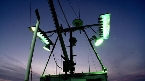 A fishing vessel turns on its outside flood lights Footage
