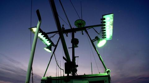A fishing vessel turns on its outside flood lights Footage