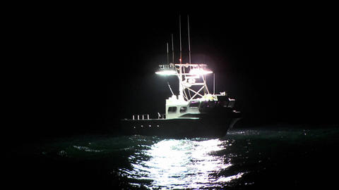 A boat sits in the water at night while a man works on the deck Footage