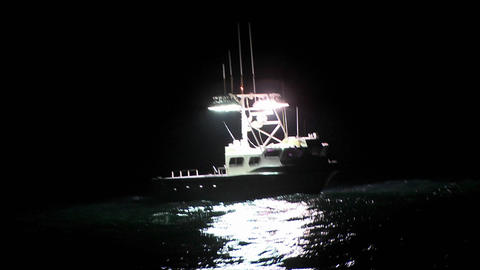 A boat sits in the water at night while a man works on... Stock Video Footage