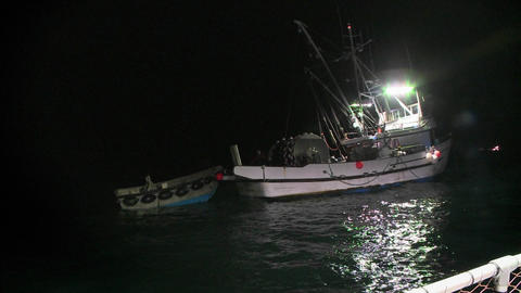 A fish-cutter works at night with its lights on Footage