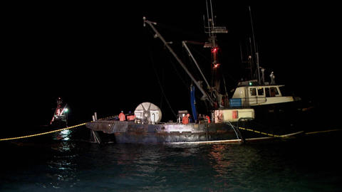 A group of men work on a small fishing boat Footage