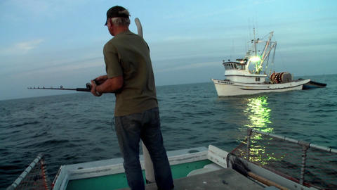 A man fishes from the back of a small boat Stock Video Footage