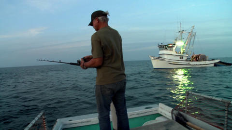 A man fishes from the back of a small boat Footage