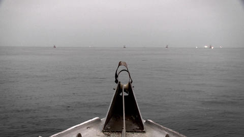 A boat passes through the water, with a swimmer and other boats in the distance Footage