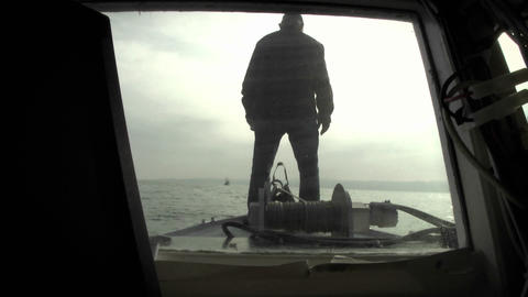 A man stands on the deck of a vessel Stock Video Footage