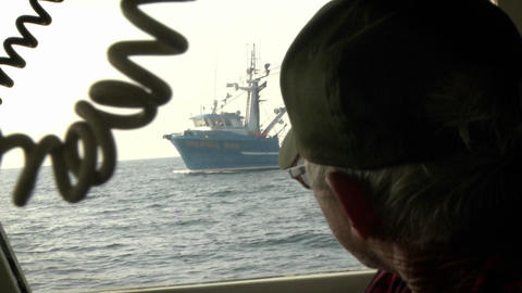 A man looks through the window of a boat at a ship with a... Stock Video Footage