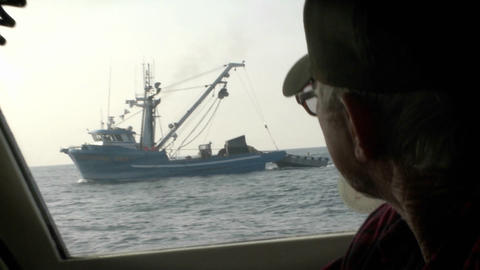 A man looks through the window of a boat at a ship with a dinghy attached Footage