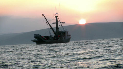 A fishing vessel navigates just off shore Stock Video Footage