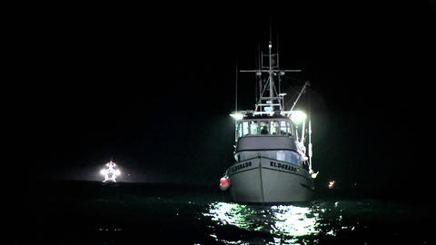 A boat sits rocking in the water at night Stock Video Footage