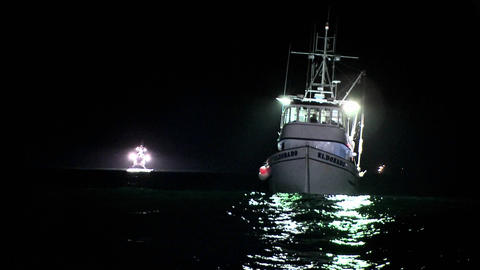 A boat sits rocking in the water at night Footage