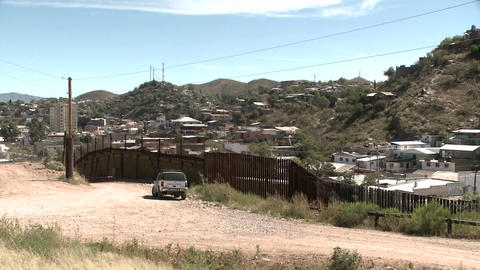 A mountainous desert community is bordered by a tall fence Stock Video Footage