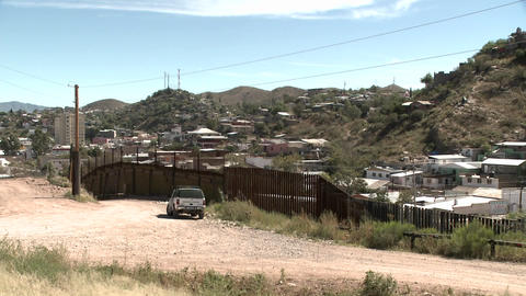 A mountainous desert community is bordered by a tall fence Footage