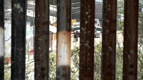 Two people down in a poor intercity community are being observed through the slats of a border fence Footage