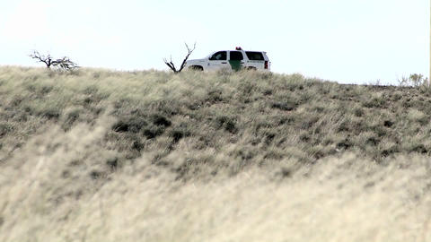 A car sits on a hill with the door open, and grass blows... Stock Video Footage
