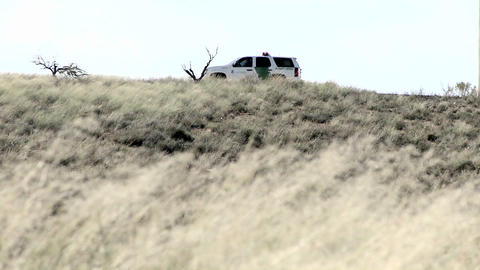 A car sits on a hill with the door open, and grass blows in the wind Footage