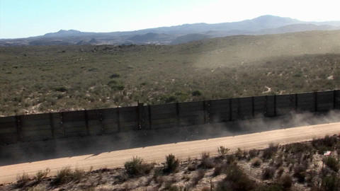 A car drives down a road bordered by a fence Stock Video Footage