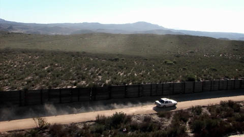 A car drives down a road bordered by a fence Footage