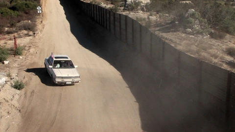 A car with a flag drives down a road behind a tall fence Stock Video Footage