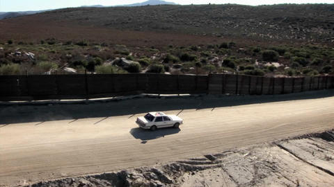 A car drives along a road bordered by a high fence Footage
