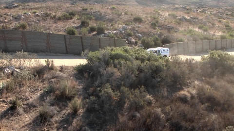 A vehicle travels up a road bordered by a tall fence Stock Video Footage