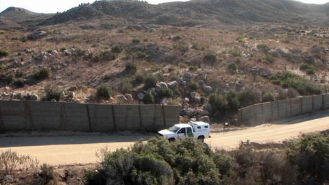 A vehicle travels up a road bordered by a tall fence Footage