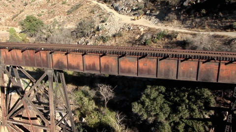 A helicopter is hovering over train tracks on a bridge... Stock Video Footage
