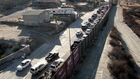 Cars are lined up in two rows along a tall fence Stock Video Footage