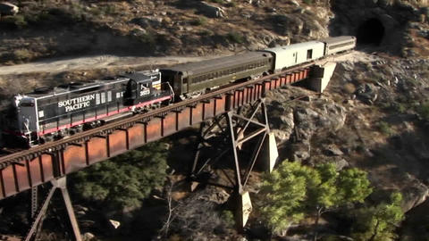 A train crosses a bridge and starts to enter into a tunnel Stock Video Footage