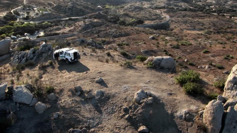 A vehicle is parked on top of a hill with doors open, and other vehicles are parked below Footage