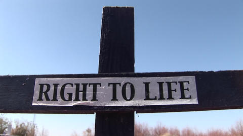 """A wooden cross has a Right to Life"""" banner attached Footage"""