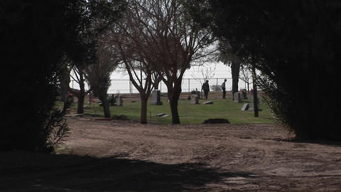 Two people are walking and looking at gravestones in a cemetery by the sea Footage