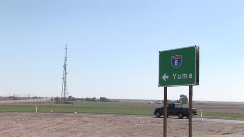 A truck drives by a road sign pointing to Yuma Stock Video Footage