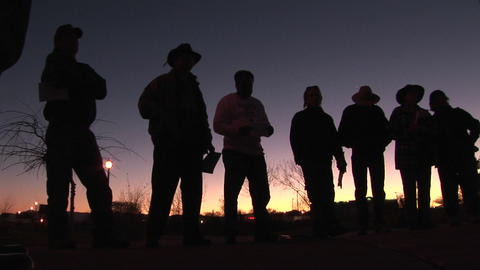 In the early morning hours, seven or eight men are standing around holding papers and waiting Footage