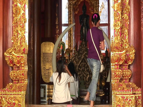 A young woman enters a Buddhist temple and sits to and... Stock Video Footage