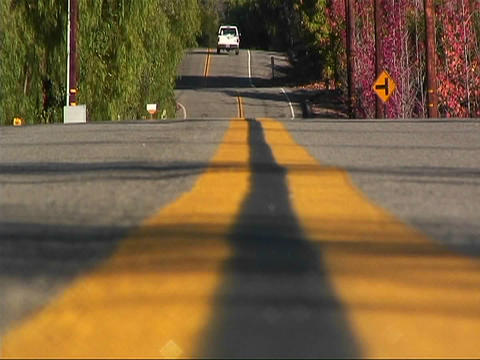 A car drives down a street in a rural area Stock Video Footage