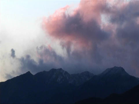 Dark clouds roll in over low mountains near sunset Stock Video Footage