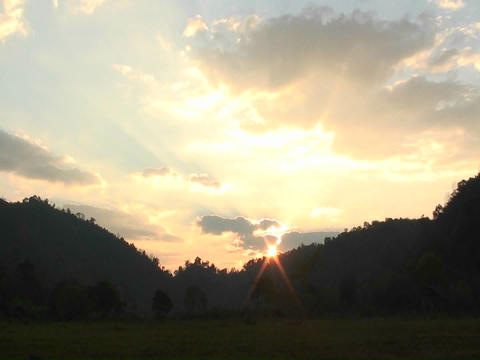 The sun rises over mountains and a body of water Stock Video Footage